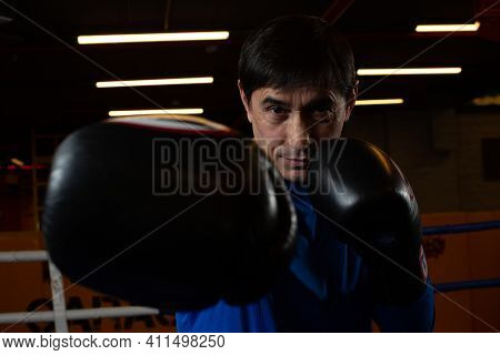 A Confident Adult Male Boxer Performs Exercises In The Ring In The Gym. Photo Of Boxers Workout. Hig