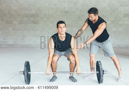 Fit Man Is Doing Barbell Exercises At Gym While A Male Instructor Is Helping Him On A Gym Routine