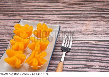 Pinched Gold Egg Yolks Or Khanom Thong Yip In The Thai Language Are Placed On A Plate With Cutlery P