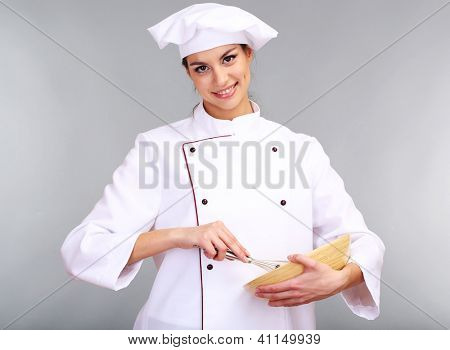 Portrait of young woman chef with wisk on grey background