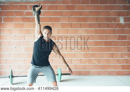Fitness Young Man Doing A Weight Training By Lifting Kettlebell. Young Athlete Doing Kettlebell Swin