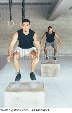 Two Fit Men Are Doing Box Jumps Exercises At Gym On A Power Routine. Healthy Lifestyle.