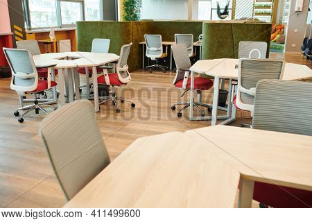 Interior of large open space office with many chairs by various kinds of tables against rest zone with couch and cushions with nobody around