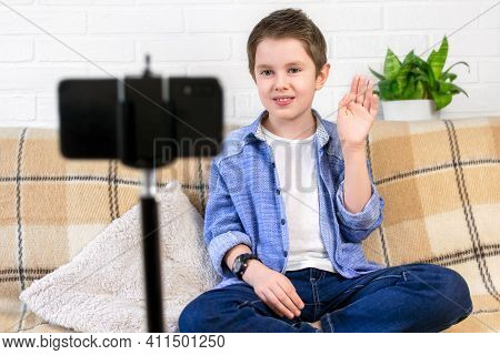 A Positive Child Is Blogging At Home, A Smiling Boy Sits On The Couch In Front Of The Camera And Rec
