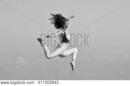 Girl Jumping High. Sport In Motion. Full Of Energy. Attractive Young Sporty Woman Is Working Out In