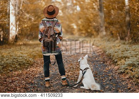Stylish Woman With Backpack Hiking With Adorable White Dog In Sunny Autumn Woods. Cute Swiss Shepher