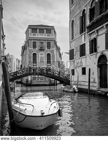 View of a venetian canal with bridge and moored motorboat, Venice, Italy. Black and white photography, cityscape