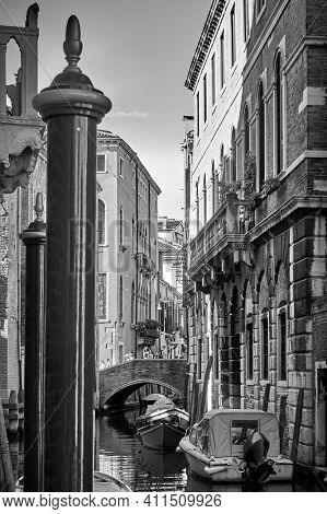 Venetian canal with mooring poles and motorboats, Venice, Italy. Black and white photography, cityscape