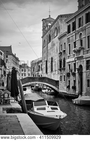 Venetian canal with bridge and moored motorboats, Venice, Italy. Black and white photography, cityscape
