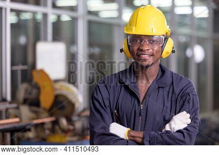 Portrait Of Cheerful Black Worker Wearing Protective Headphones Posing Looking At Camera And Enjoyin