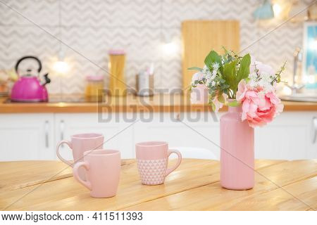 Pink Vase With Flowers And Mugs For Tea On The Table In A Light Kitchen In The Scandinavian Style.