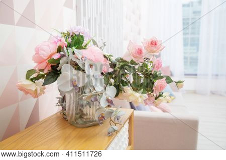 A Vase Of Flowers On A Chest Of Drawers Near The Wall With A Geometric Pattern In A Light Pink Livin