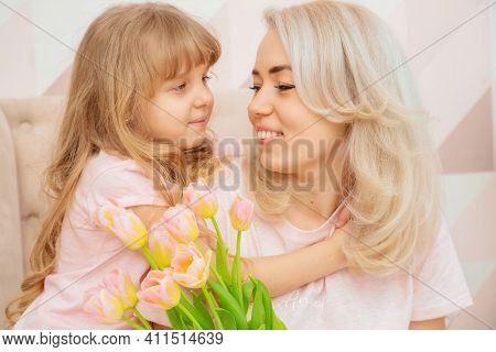 Happy Mother's Day! Child Daughter Congratulates Mom And Give Her Bouquet Of Flowers Tulips In Pink