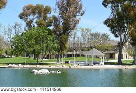 IRVINE, CA - MARCH 24, 2017: Heritage Park Community Center with pond and Gazebo. The park features, pools, sports fields, Mulit-use buildings, lawns, pond, amphitheater, and more.