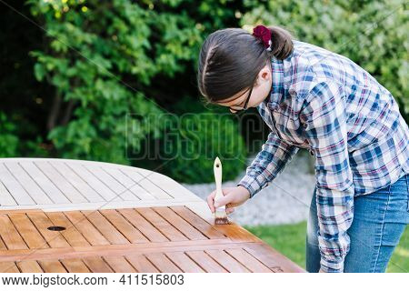 Young Woman Painting Wooden Exotic Wood Table In The Garden With A Brush - Shallow Depth Of Field