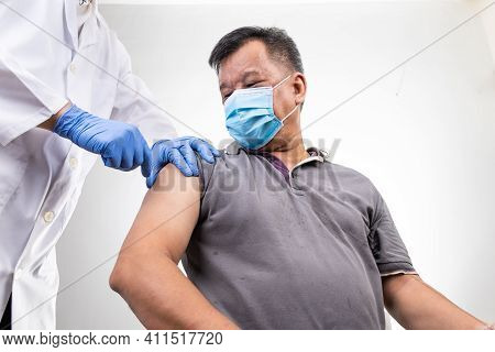 Asian Middle Age Man Receiving Covid-19 Vaccine Injection Onto The Arm