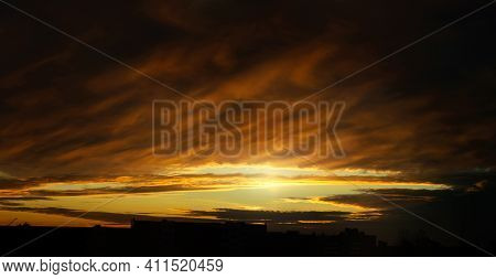 Sunset sky background,dramatic sunset sky with evening sky clouds lit by bright sunlight - city sunset sky landscape view,sunset view,sunset sky,sunset scene,sunset landscape,sunset in the city