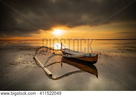 Seascape. Fisherman Boat. Traditional Balinese Boat Jukung. Fishing Boat At The Beach During Sunrise