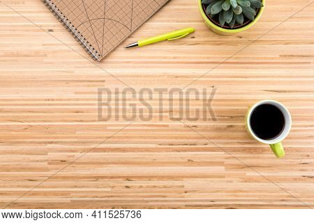 Wooden desk  background with stationery, coffee cup, potted succulent plant and copy space