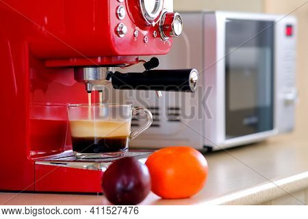 Two Streams Of Espresso Coffee On The Espresso Machine Are Poured Into A Transparent Cup. Aromatic C