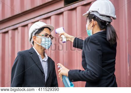 Female Foreman Wearing A Mask Measures The Temperature For A Male Foreman In A Suit. They Stood And
