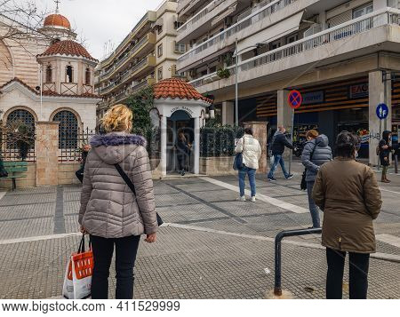 Thessaloniki, Greece March 6 2021: Crowd Wearing Covid-19 Masks Keep Their Distance Outside A Chapel