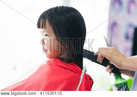 Asian Girl Cut Hair At Beauty Salon. The Hairdresser Is Hand Gently Brushes The Hair With Skill. In