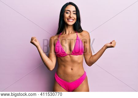 Beautiful hispanic woman wearing bikini very happy and excited doing winner gesture with arms raised, smiling and screaming for success. celebration concept.