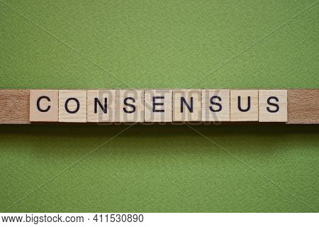 Gray Word Consensus Made Of Wooden Square Letters On Green Background