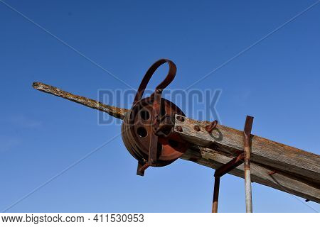 A Homemade Vintage  Rusty Pulley Is Attached To Aging Wooden Beams