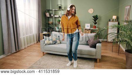 Caucasian Young Beautiful Joyful Woman Dancing In Modern Living Room In House Alone Listening To Mus