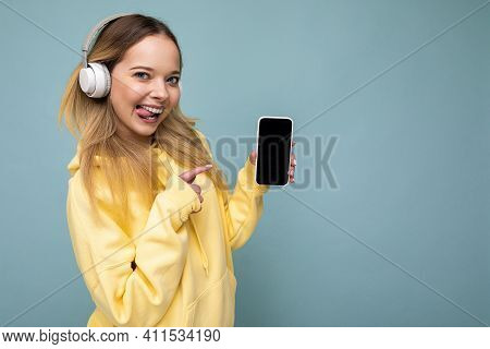 Side-profile Sexy Beautiful Young Blonde Woman Wearing Yellow Stylish Hoodie Isolated On Blue Backgr