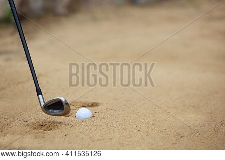 Golf Ball And Club In Sand Bunker At Golf Course