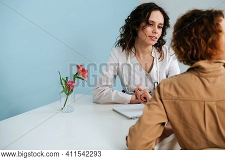 Pretty Doctor Attending To A Patient In Her Office, Looking At Her. Over Blue Background. She Wears