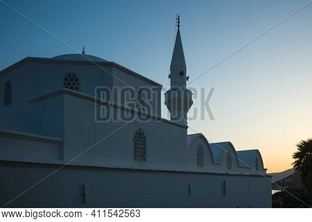 Central mosque in old town of Kalkan has been converted from building of Greek Orthodox Church, Classical greek architecture with minaret at dusk, Turkey