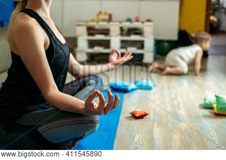 Mindfulness Meditation Concept. Young Woman, Mother Practicing Yoga At Home Sitting In Lotus Pose, M