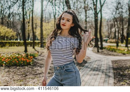 Outdoor Portrait Of Young Teen Brunette Girl With Curly Hair. Hispanic, Latino Teenager Girl In Park