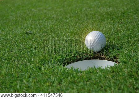 Golf Ball And Golf Hole On Green Grass. A Golf Ball Sits At The Lip Of The Hole On The Putting Green