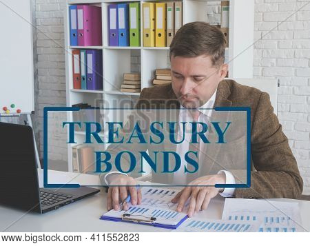 Treasury Bonds Concept. Man In Suit Works With Papers.