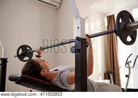 Young Woman Lying On An Athletic Bench And Pressing A Barbell During A Bodybuilding Workout. Bodybui