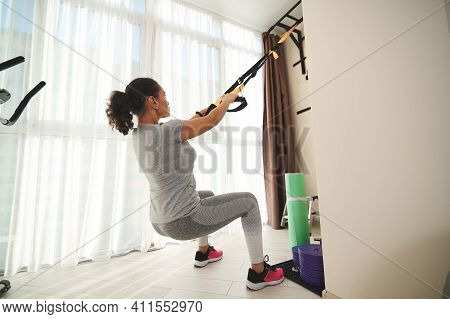 A Sporty Girl Performing Suspension Training With Fitness Straps At Home. Fit Woman Training Leg Mus