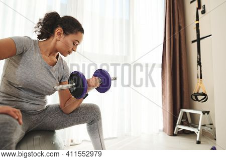 Young African American Woman Doing Biceps Exercises With Dumbbells At Gym Sitting On Sports Ball