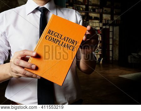 Regulatory Compliance Book In The Hands Of A Man With A Tie.