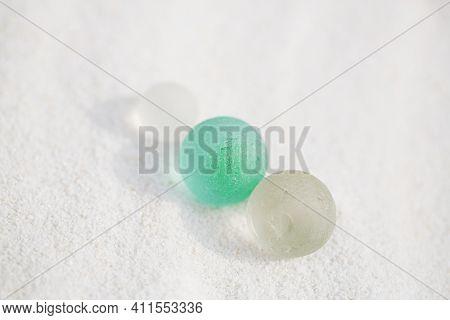 three sea glass marbles  on white sand beach