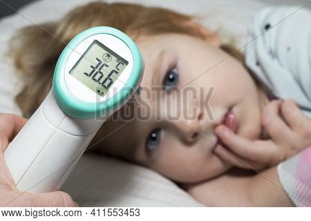 A Parent Measures Temperature Of His Kid With Contactless Thermometer.