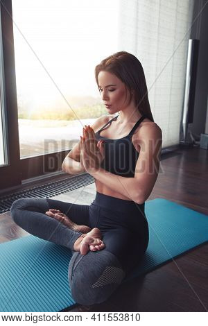 Caucasian Woman In Harmony Doing Yoga In Lotus Sit At Home, Eyes Closed, Relaxing And Mental Health