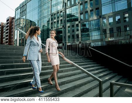 Business, people and lifestyle concept: Two smiling business women talking while walking down stairs near modern office building.