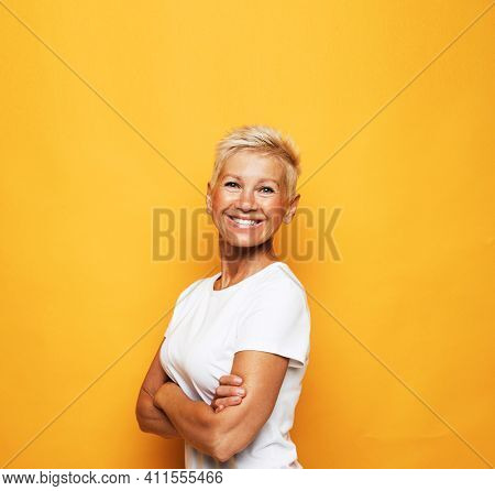 Positive human emotions and reaction. Portrait of carefree happy senior woman with stylish short hair looking at camera with broad cheerful smile, wearing white shirt over yellow background