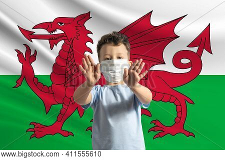 Little White Boy In A Protective Mask On The Background Of The Flag Of Wales. Makes A Stop Sign With
