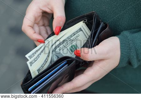 Woman Hands With Red Nails Holds Black Mens Purse With Many Us Hundred Dollars Bills. Concept Of Sal